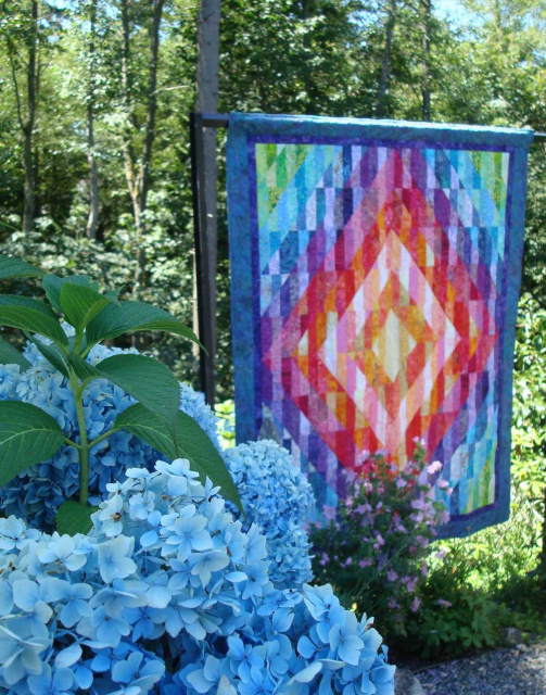 picture of beautiful colorful quilt next to bright blue hydrangeas